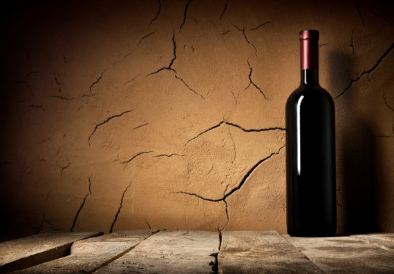 Bottle of cabernet in cellar near clay wall