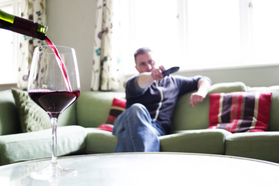 A glass of wine being poured whilst a man flicks channels using a remote control