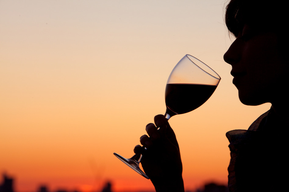 Woman drinking a glass of wine by the sunset