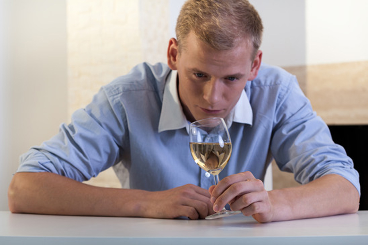 Young man with a glass of white wine on the table
