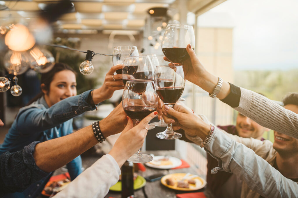 people toasting with red wine